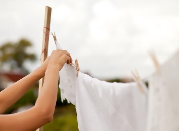 Mão de uma mulher lavando e pendurando roupa ao ar livre em um dia ensolarado.