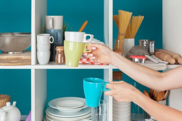 Mão de uma mulher levando utensílios de cozinha de uma prateleira de cozinha