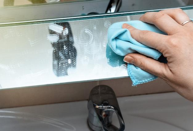 Mão de uma mulher, limpando o vidro com uma esponja. limpando o banheiro.