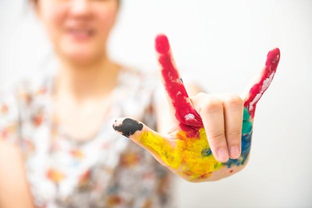 Mão de uma mulher, manchada com tinta multicolorida, isolada no fundo branco. menina com rosto sorridente mostra pinturas coloridas à mão. eu amo você, gesto.