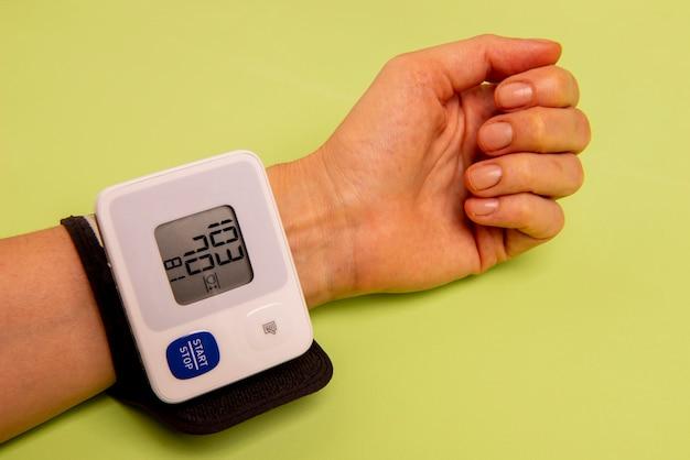 Mão de uma mulher medindo sua pressão arterial.