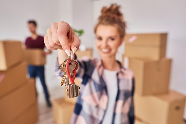 Mão de uma mulher mostrando as chaves do novo apartamento