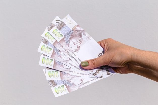 Mão de uma mulher mostrando notas de duzentos reais em superfície isolada
