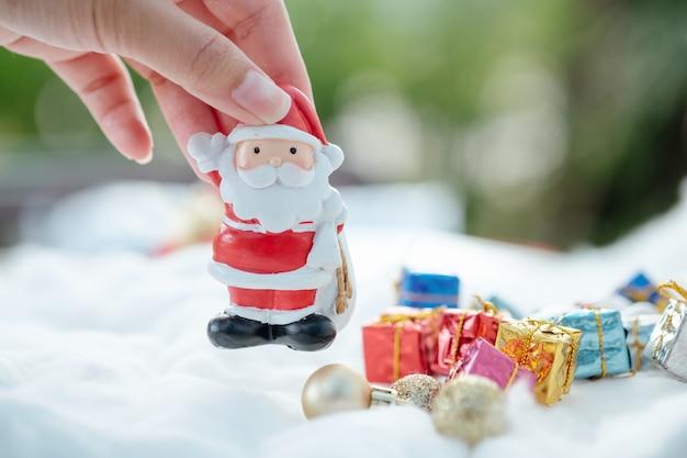 Mão de uma mulher organizando personagens coloridos de natal e decorações.
