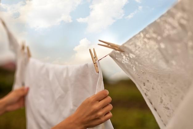 Mão de uma mulher pendurando roupa ao ar livre em um dia ensolarado