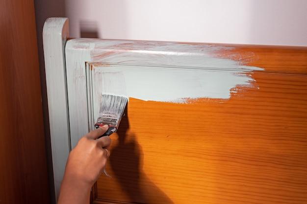 Mão de uma mulher pintando móveis de madeira para reforma em casa