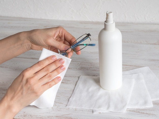 Mão de uma mulher que limpa vidros com toalhetes desinfetantes devido à pandemia do vírus de corona
