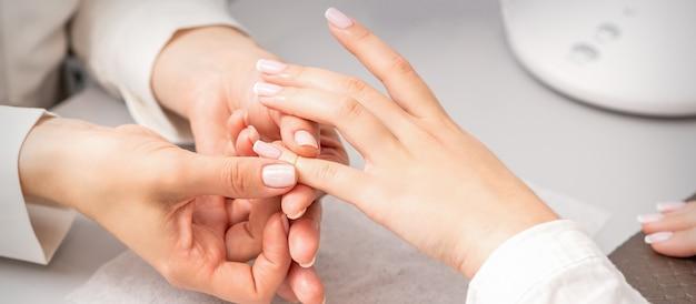 Mão de uma mulher recebendo massagem com os dedos em um salão de beleza