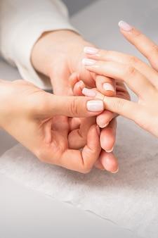 Mão de uma mulher recebendo massagem nos dedos em um salão de beleza. tratamento de manicure em spa de beleza