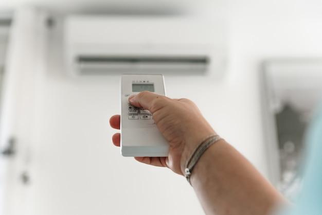 Mão de uma mulher regulando o ar condicionado com o controle remoto.