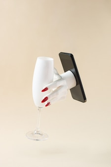 Mão de uma mulher saindo do telefone segurando uma taça de champanhe