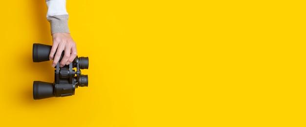 Mão de uma mulher segura binóculos em um fundo amarelo brilhante. bandeira.