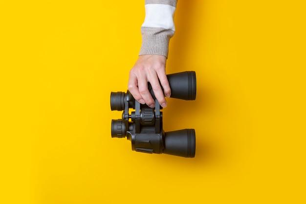 Mão de uma mulher segura binóculos em um fundo amarelo brilhante.