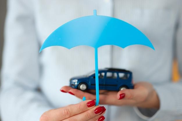 Mão de uma mulher segura o carro e um guarda-chuva. conceito de seguro de veículos