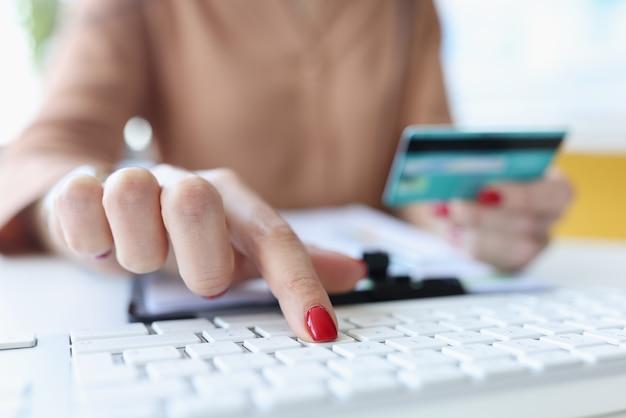 Mão de uma mulher segura o cartão do banco e funciona no teclado do computador