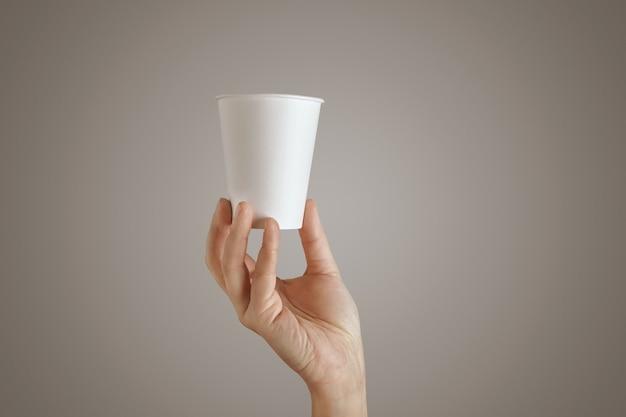 Mão de uma mulher segura o copo de papel vazio vazio da parte inferior, apresentação no centro, vista lateral, isolado, irreconhecível