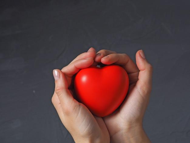 Mão de uma mulher segura um coração vermelho