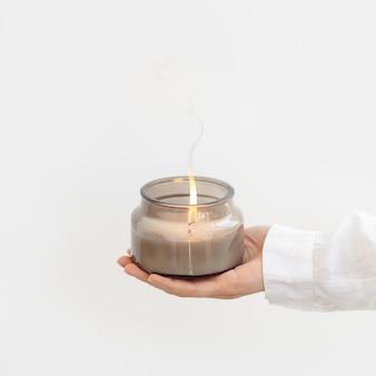 Mão de uma mulher segura uma vela perfumada acesa em um frasco de vidro cinza com ingredientes naturais