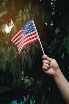 Mão de uma mulher segurando a bandeira dos eua na floresta verde. 4 de julho dia da independência americana