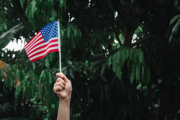 Mão de uma mulher segurando a bandeira dos eua na floresta verde