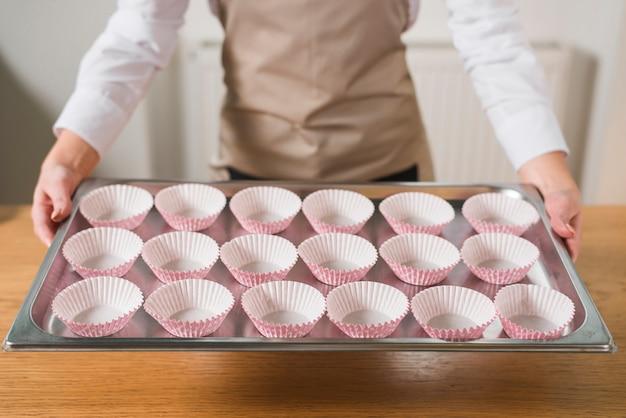 Mão de uma mulher segurando a bandeja de um caso de cupcake vazio
