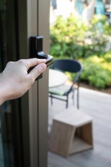 Mão de uma mulher segurando a barra da porta para abrir a porta