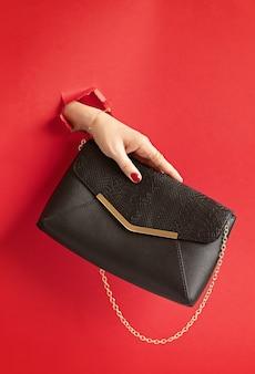 Mão de uma mulher segurando a bolsa da moda pelo buraco na parede de papel vermelho. chic, estilo, coleção de moda, tendências, conceito de blog de beleza
