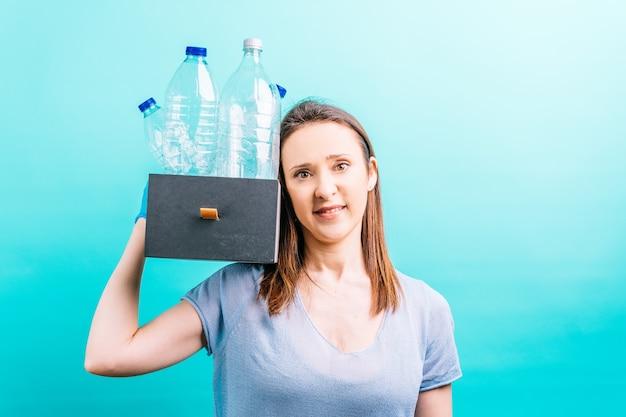 Mão de uma mulher segurando a caixa com garrafas de plástico para reciclagem. conceito de reciclagem. cuidado ambiental