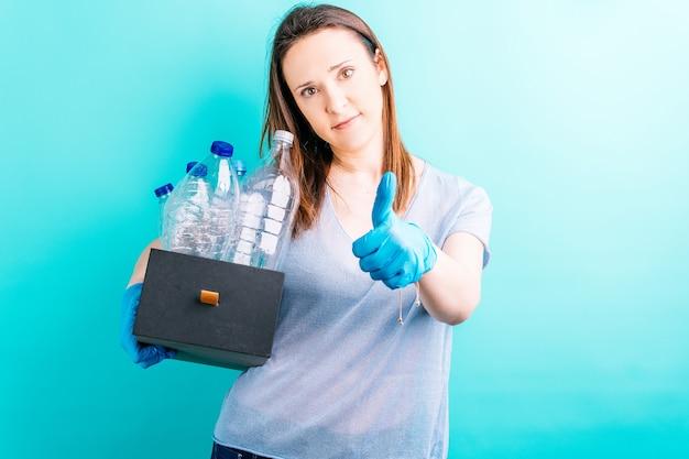 Mão de uma mulher segurando a caixa com garrafas de plástico para reciclagem, levantando o polegar. conceito de reciclagem. cuidado ambiental