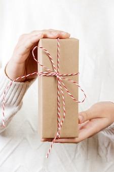 Mão de uma mulher segurando a caixa de presente para o natal