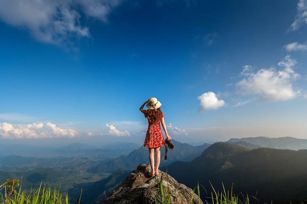 Mão de uma mulher segurando a câmera e em pé no topo da rocha na natureza. conceito de viagens.