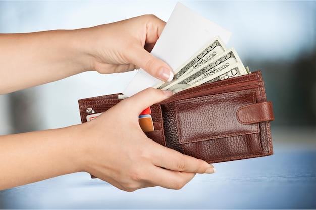 Mão de uma mulher segurando a carteira com dólares. conceito de negócios