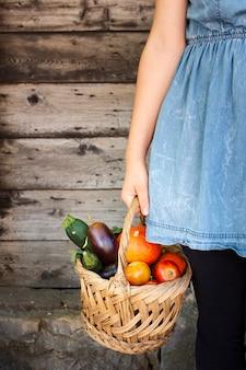 Mão de uma mulher segurando a cesta cheia com legumes
