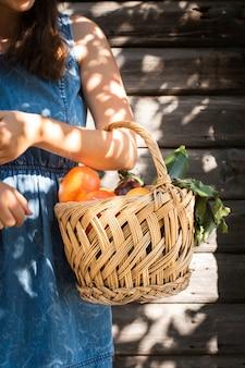 Mão de uma mulher segurando a cesta com legumes