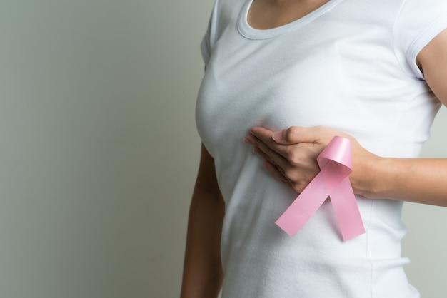 Mão de uma mulher segurando a conscientização do câncer de mama de fita rosa.