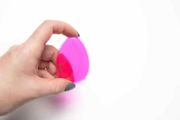 Mão de uma mulher segurando a esponja de base de silicone em um fundo branco. foto de close
