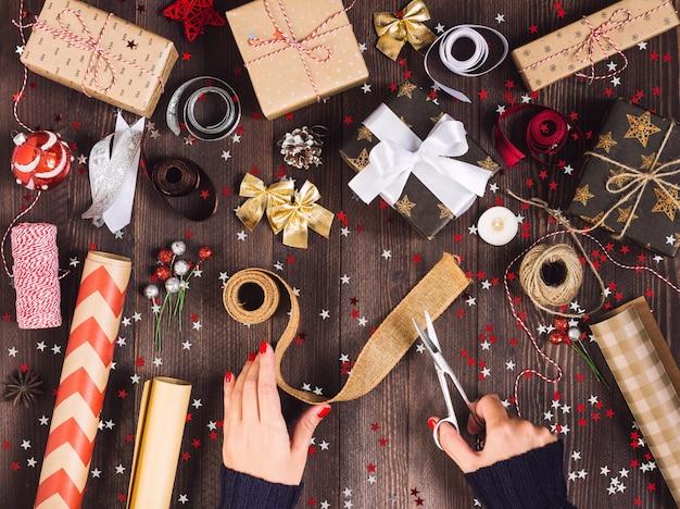 Mão de uma mulher segurando a fita de serapilheira com uma tesoura para cortar e embalar a caixa de presente de natal