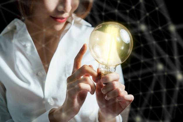 Mão de uma mulher segurando a lâmpada. conceito de idéia com inspiração. idéia de conexão de negócios.