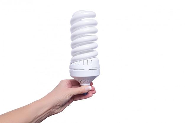 Mão de uma mulher segurando a lâmpada de poupança de energia, isolada