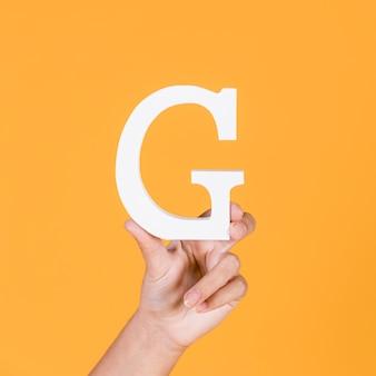 Mão de uma mulher segurando a letra maiúscula branca g