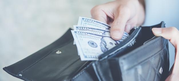 Mão de uma mulher segurando a moeda americana de cinco notas de dólar, gastos e compras