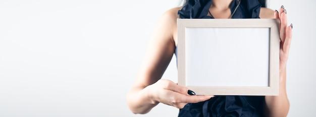 Mão de uma mulher segurando a moldura em branco.