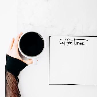 Mão de uma mulher segurando a xícara de café com texto manuscrito no caderno sobre a mesa