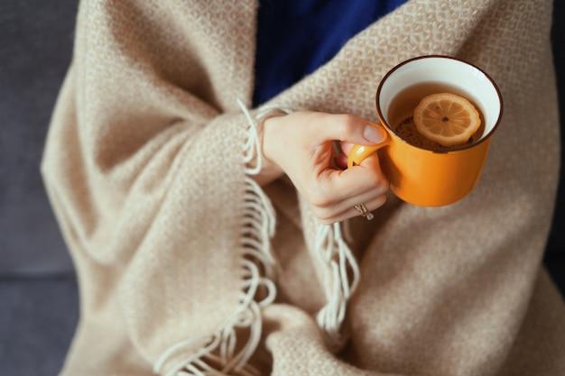 Mão de uma mulher segurando a xícara de chá com limão