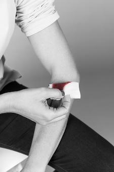 Mão de uma mulher segurando bandagem médica no pulso de sangramento