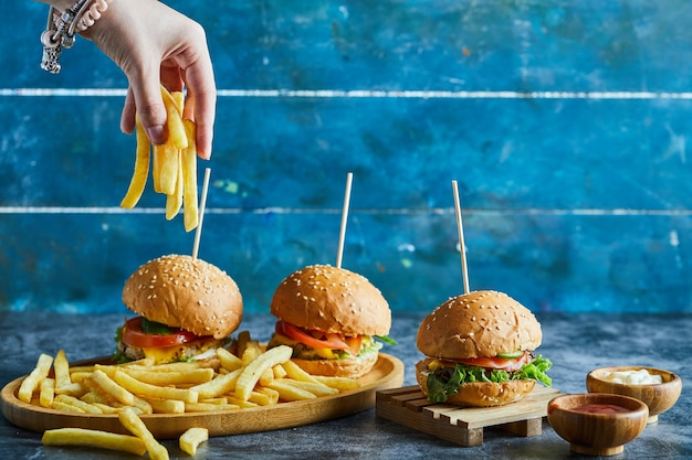 Mão de uma mulher segurando batata frita com três cheeseburgers, ketchup e maionese em um prato de madeira