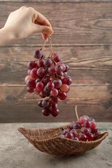 Mão de uma mulher segurando cacho de uvas vermelhas em fundo de madeira.