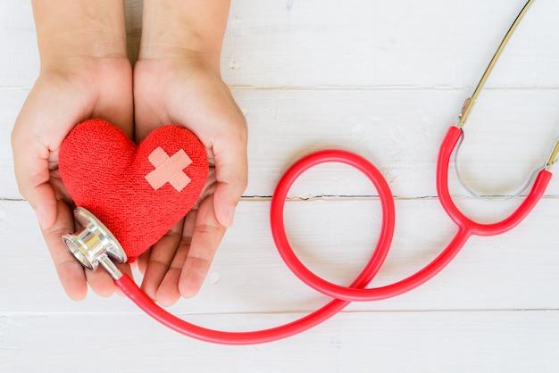 Mão de uma mulher segurando coração vermelho com estetoscópio no fundo branco de madeira