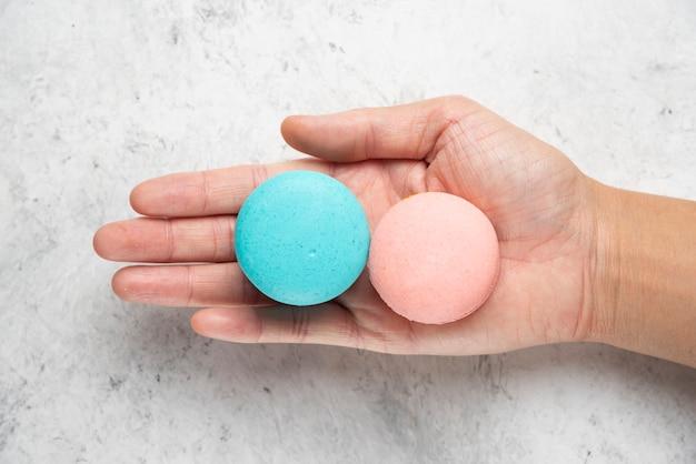 Mão de uma mulher segurando dois saborosos macarons na superfície de mármore.
