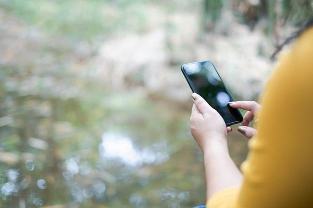 Mão de uma mulher segurando e usando o smartphone, tela preta